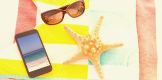 Composite image of close up of starfish with sunglasses and mobile phone kept on beach blanket Royalty Free Stock Photo