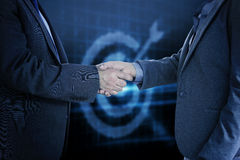 Composite image of close up on two businesspeople shaking hands Stock Images