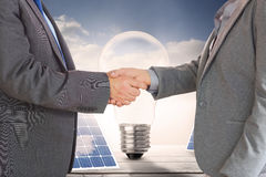 Composite image of close up on two businesspeople shaking hands Royalty Free Stock Photos