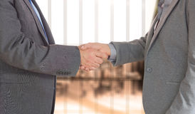 Composite image of close up on two businesspeople shaking hands Royalty Free Stock Image