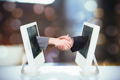 Composite image of close up of two businesspeople shaking their hands Stock Image