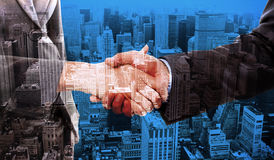 Composite image of close up of two businesspeople shaking their hands Royalty Free Stock Photography