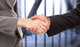 Composite image of close up of two businesspeople shaking their hands Stock Photography