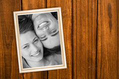 Composite image of close up of two friends looking upwards while lying head to shoulder Royalty Free Stock Images