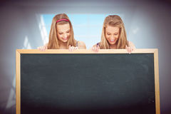 Composite image of close up of two young women holding a blank board Royalty Free Stock Images