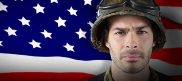 Composite image of close up of unsmiling soldier. Close up of unsmiling soldier against highly detailed 3d render of an american flag Stock Photo