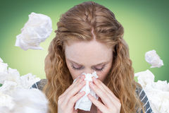 Composite image of close-up of woman blowing nose into tissue. Close-up of woman blowing nose into tissue against green vignette Stock Image
