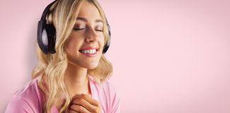Composite image of close up of a woman listening to music Stock Photo