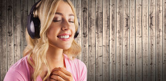 Composite image of close up of a woman listening to music Stock Image