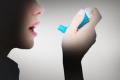 Composite image of close up of a woman using an asthma inhaler Stock Photography