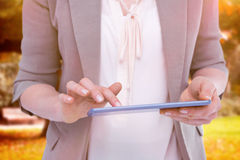 Composite image of close up of woman using tablet Stock Photography