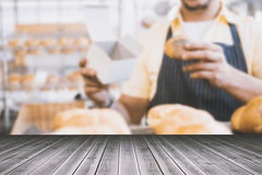 Composite image of close-up of wooden flooring. Close-up of wooden flooring against worker in apron holding box and bread stock photos