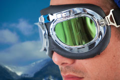 Composite image of close up of young man wearing aviator goggles. Close up of young man wearing aviator goggles against scenic view of snowy mountain range royalty free stock photos