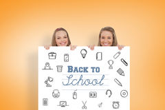 Composite image of close up of young women behind a blank sign Royalty Free Stock Photos
