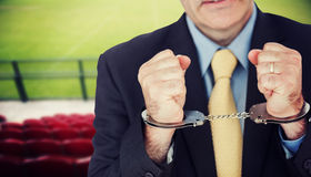 Composite image of closeup of businessman with handcuffed hands Royalty Free Stock Images