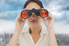 Composite image of closeup of a businesswoman looking through binoculars Stock Photography