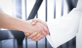 Composite image of closeup of a doctor and patient shaking hands Royalty Free Stock Images