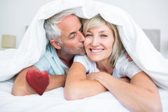 Composite image of closeup of mature man kissing womans cheek in bed. Closeup of mature men kissing womans cheek in bed against red heart Royalty Free Stock Photo