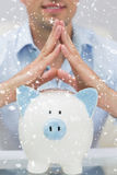 Composite image of closeup mid section man with piggy bank at home Stock Photography
