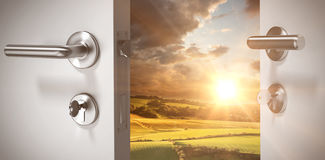 Composite image of closeup of wooden door with metallic doorknob. Closeup of wooden door with metallic doorknob against country scene Royalty Free Stock Photo