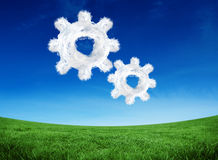 Composite image of cloud cog and wheel. Cloud cog and wheel against green field under blue sky Royalty Free Stock Photography