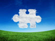 Composite image of cloud jigsaw piece. Cloud jigsaw piece against green field under blue sky Royalty Free Stock Photography