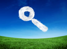 Composite image of cloud magnifying glass. Cloud magnifying glass against green field under blue sky Royalty Free Stock Photos