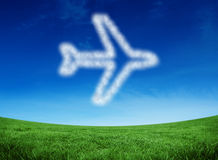 Composite image of cloud in shape of airplane. Cloud in shape of airplane against green field under blue sky Stock Photos