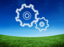Composite image of cloud in shape of cogs and wheels. Cloud in shape of cogs and wheels against green field under blue sky Royalty Free Stock Photography
