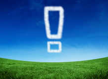 Composite image of cloud in shape of exclamation mark. Cloud in shape of exclamation mark against green field under blue sky Royalty Free Stock Image