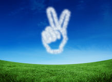 Composite image of cloud in shape of hand making peace sign. Cloud in shape of hand making peace sign against green field under blue sky Stock Images