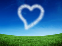 Composite image of cloud in shape of heart. Cloud in shape of heart against green field under blue sky Stock Photo