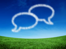 Composite image of cloud in shape of speech bubbles. Cloud in shape of speech bubbles against green field under blue sky Royalty Free Stock Photo