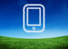 Composite image of cloud in shape of tablet pc. Cloud in shape of tablet pc against green field under blue sky Royalty Free Stock Photography