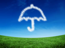 Composite image of cloud in shape of umbrella. Cloud in shape of umbrella against green field under blue sky Royalty Free Stock Image