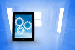Composite image of cogs in clouds on tablet screen Stock Images