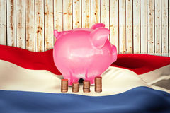 Composite image of coins and piggy bank Stock Images