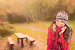 Composite image of cold redhead wearing coat and hat Royalty Free Stock Image