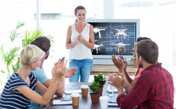 Composite image of colleagues clapping hands in a meeting. Colleagues clapping hands in a meeting against composite image of four drones royalty free stock images