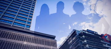 Composite image of colleagues standing against white background. Colleagues standing against white background against building against cloudy sky Stock Images