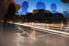 Composite image of colleagues standing against white background. Colleagues standing against white background against light trails on city street Stock Photography