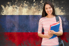 Composite image of college girl holding books with blurred students in park Royalty Free Stock Images
