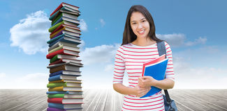 Composite image of college girl holding books with blurred students in park. College girl holding books with blurred students in park against stack of books royalty free stock image