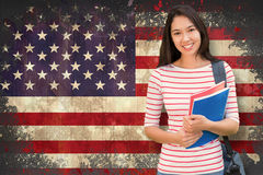 Composite image of college girl holding books with blurred students in park Stock Photo