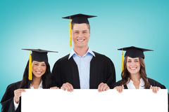 Composite image of college graduates showing card Royalty Free Stock Images