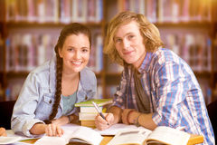Composite image of college students doing homework in library Stock Image