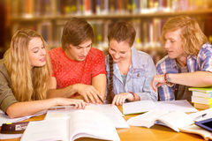 Composite image of college students doing homework in library Stock Photo