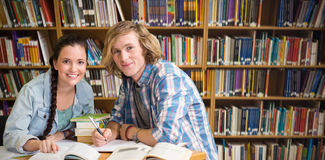 Composite image of college students doing homework in library. College students doing homework in library against various books on shelf Stock Photo