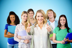 Composite image of college students gesturing thumbs up. College students gesturing thumbs up against blue background with vignette Royalty Free Stock Images
