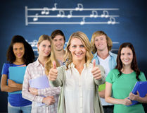 Composite image of college students gesturing thumbs up. College students gesturing thumbs up against blue chalkboard Royalty Free Stock Photo